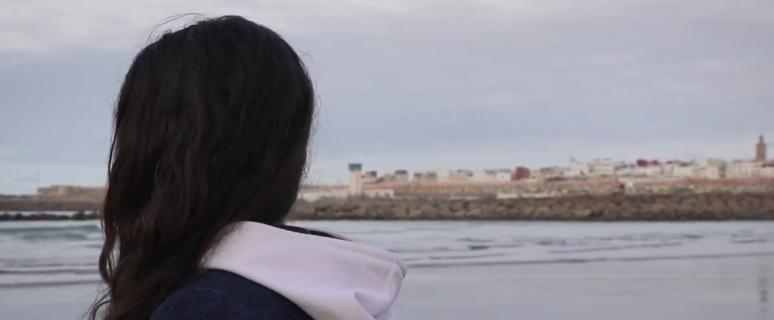 una mujer de pelo largo de espaldas, al fondo se ve una ciudad de Marruecos