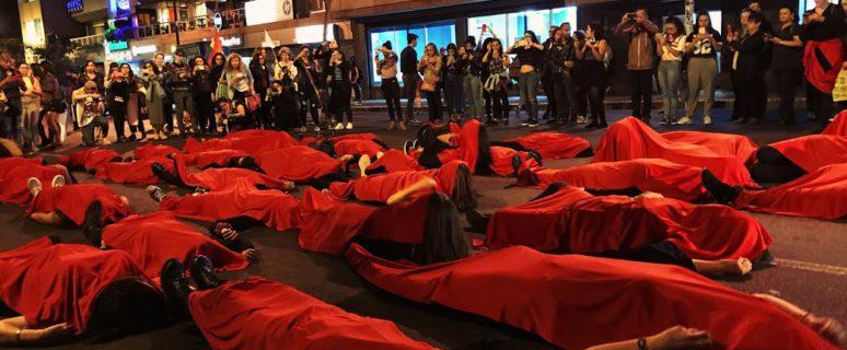 Muchas mujeres tumbadas en el suelo tapadas de rojo.