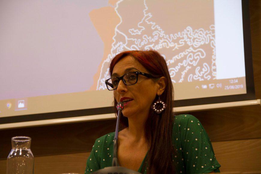 Helena Maleno sentada en una mesa hablando a través de un micro en una conferencia