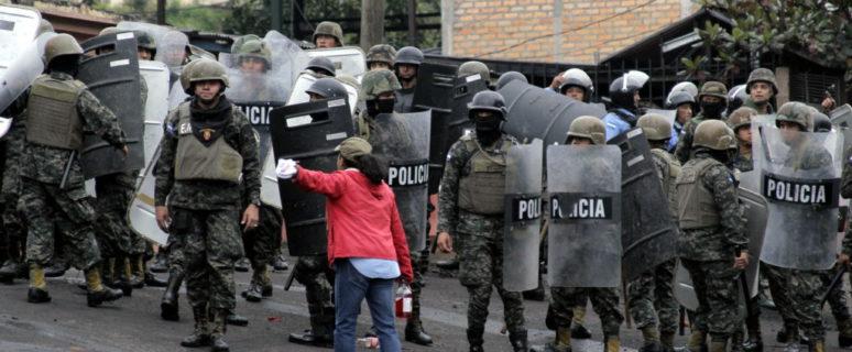 una mujer con chaqueta roja se enfrenta a un montón de policías armados