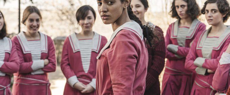Un grupo de alumnas vestidas con uniformes de los años 20 de color rosa. En el medio una alumna racializada