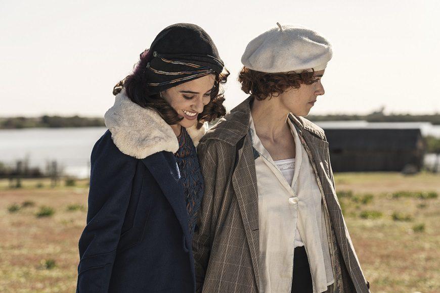 dos mujeres en el centro de la imagen, vestidas de la manera típica de los años 20