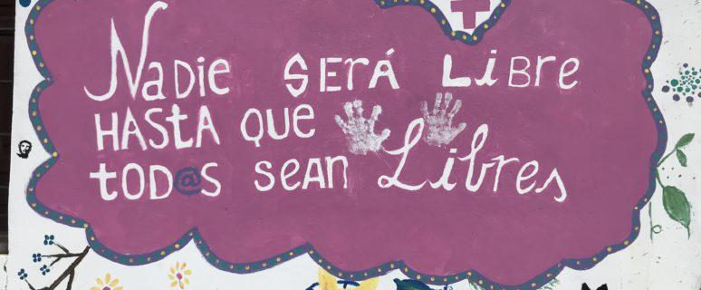 Un cartel que es una nube rosa en la que se puede leer en letras en blanco Nadie está libre hasta que todos sean libres