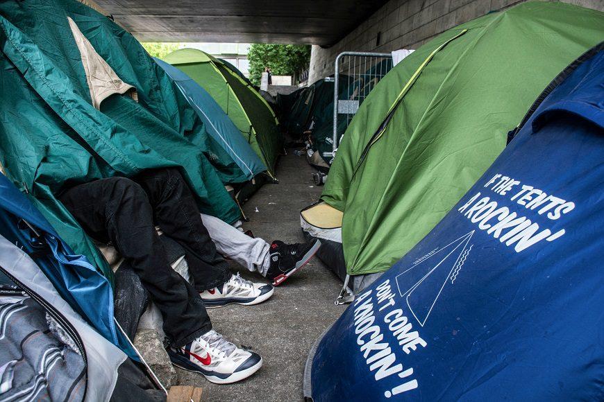 se ven partes de tiendas de campaña y se ven los pies de varias personas