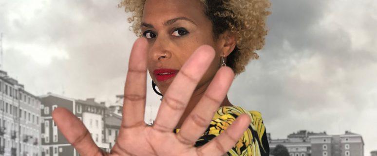 una mujer con una mano abierta en primer plano en señal de stop mira a la cámara. Tiene el pelo corto y rizado