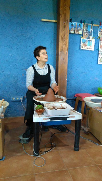 Una mujer explica cosas mientras moldea cerámica con las manos.