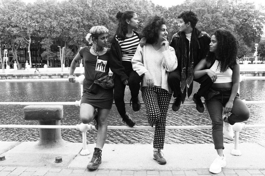 Fotografía en blanco y negro. Cinco mujeres posan apoyadas en una barandilla de la ría