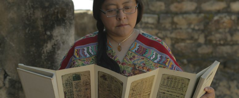 Un a mujer lee un trípico. Lleva el pelo recogido en con una trenza echada para un lado y gafas.