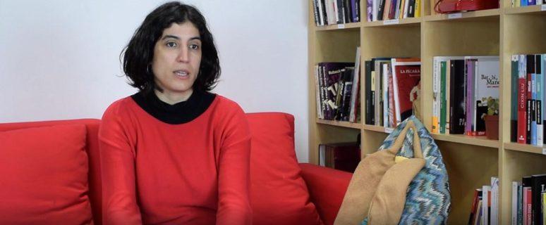Una mujer sentada en un sofá. Al lado derecho hay una estantería con libros