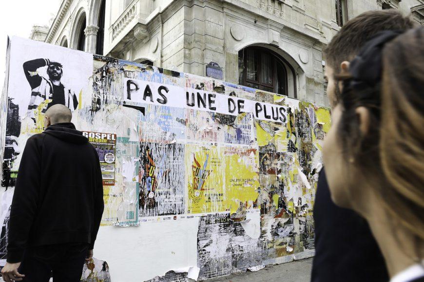 Una pared llena de carteles y la gente está pasando por delante. Francia