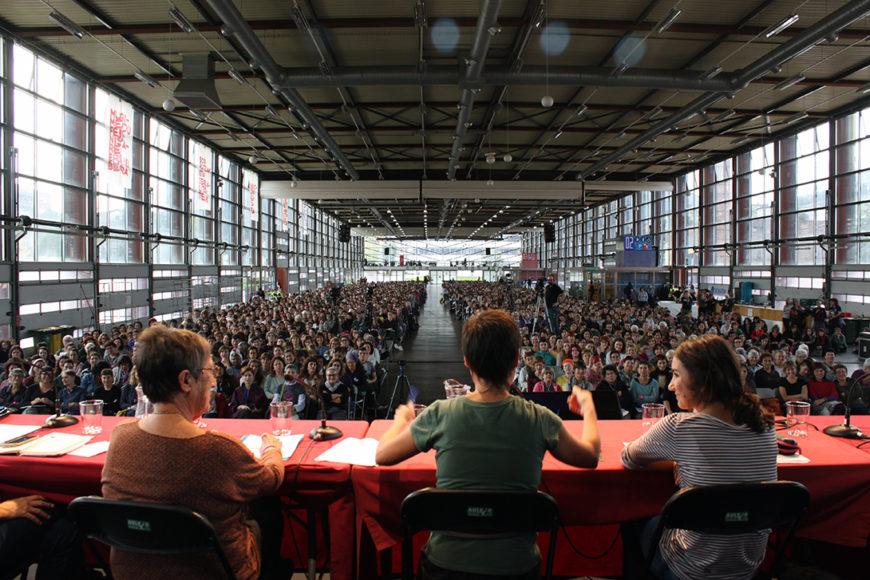 En la imagen se ve, en primer plano, a tres ponentes de la mesa sentadas de espaldas y con las 3.000 asistentes sentadas de frente en un pabellón.