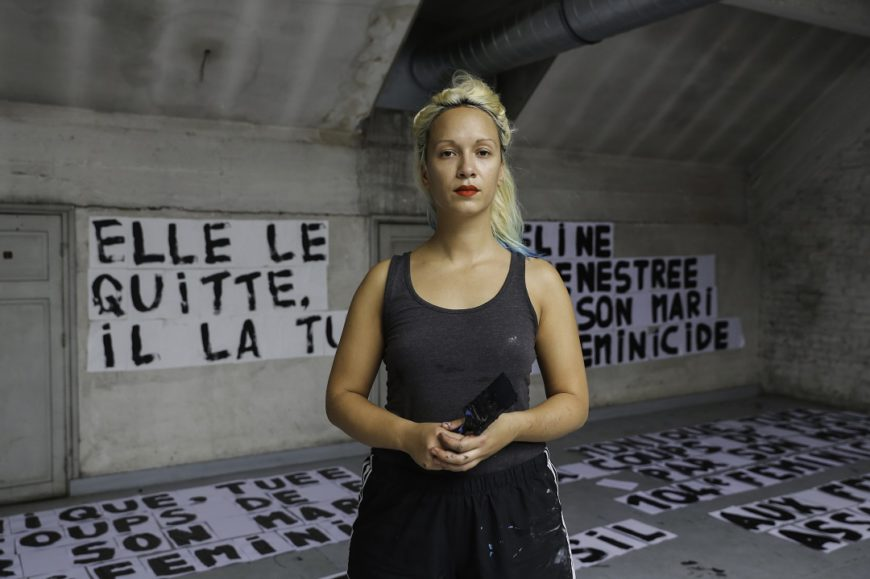 en mitad de la imagen una mujer posa, con un pincel en la mano, al fondo se ven carteles que ha hecho. Francia