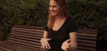 una mujer sentada en un banco de madera de la calle habla, como se nota en la expresión de las manos y la cara. Van de negro y en manga corta y el tiene le pelo largo, pelirrojo y parcialmente recogido