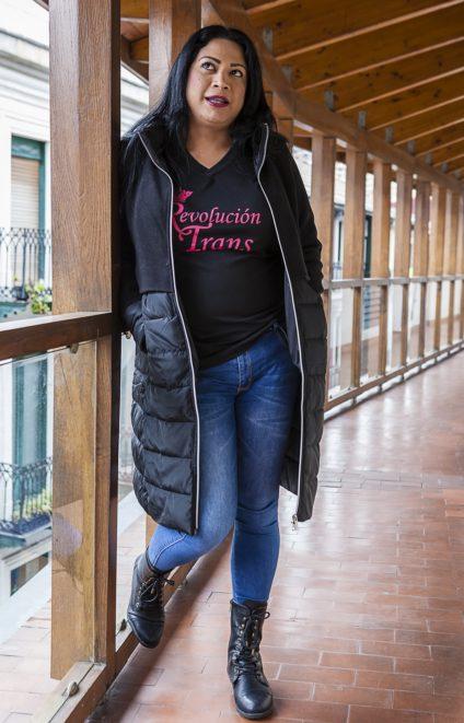 una mujer de cuerpo entero apoyada en una estructura de madera. En la camiseta que lleva debajo del abrigo se lee 'revolución trans'