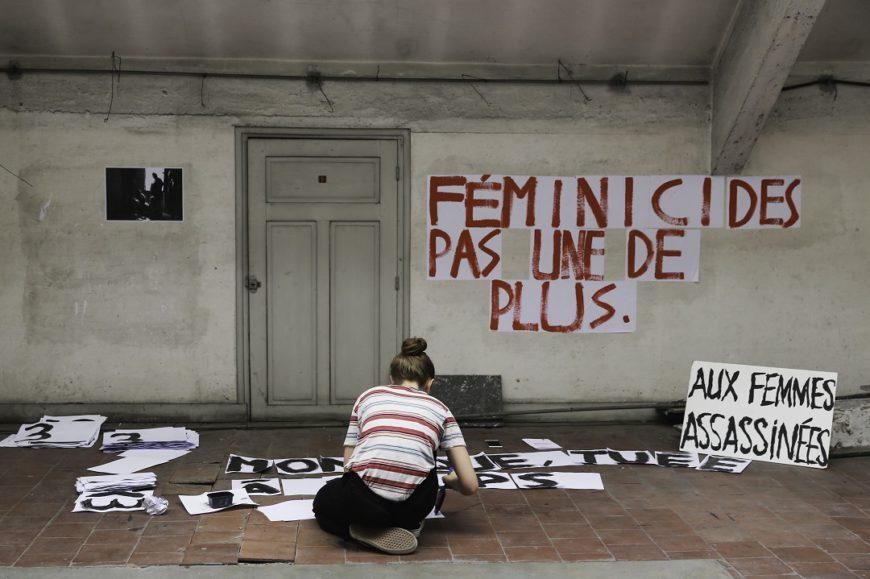 una sala casi vacía, con un cartel con letras rojas y de rodillas y de espaldas una mujer hacer un cartel en el suelo. Francia
