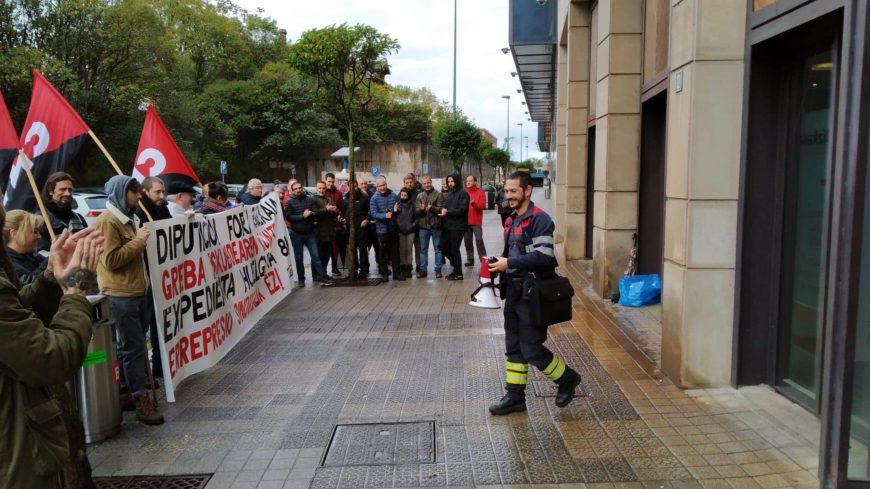 en la calle un grupo de personas porta una pancarta. Del otro lado está solo el bombero al que apoyan