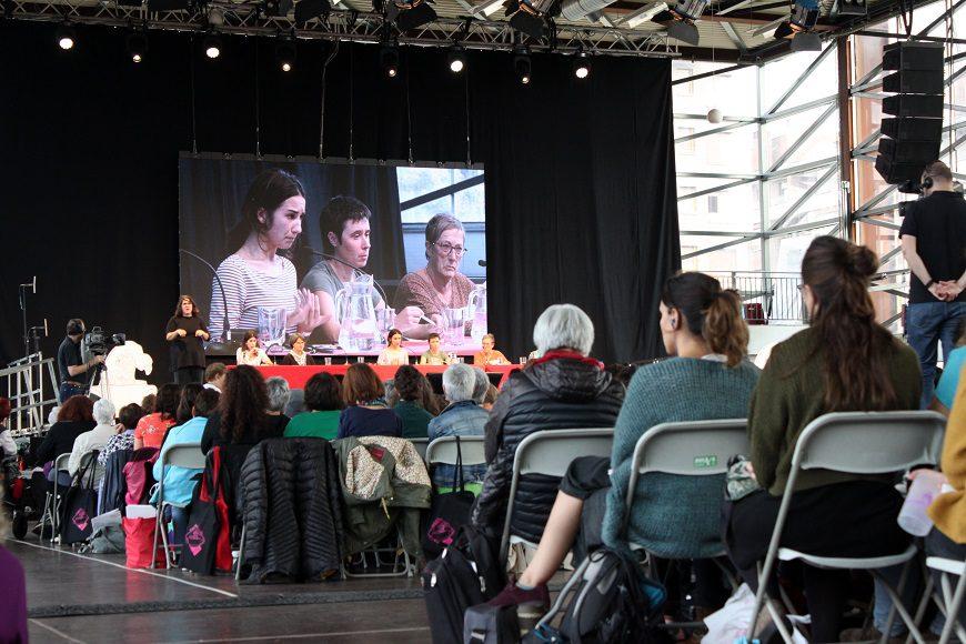 en primer plano mujeres sentadas, al fondo se ve una pantalla con tres de las ponentes de la mesa de inicio