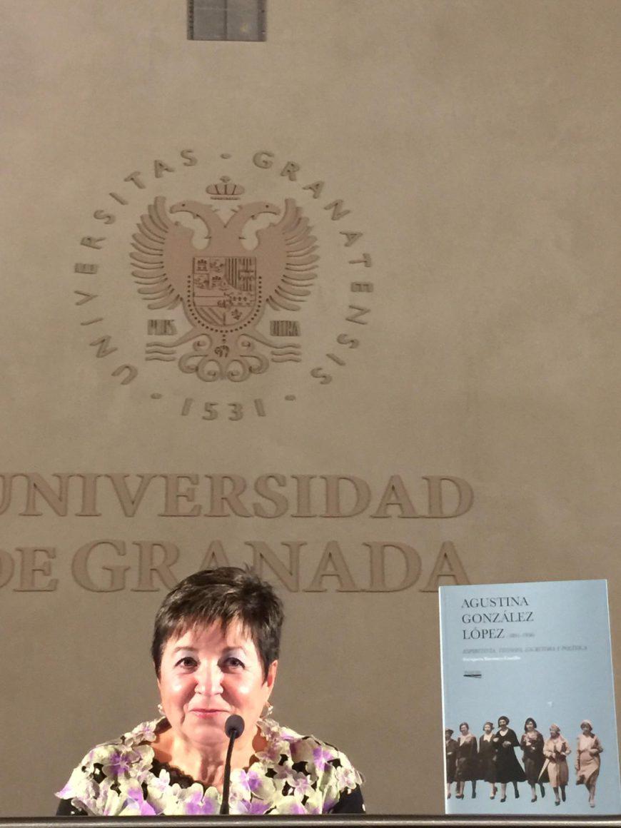 Una mujer de hombros para arriba, detrás de una mesa junto al libro que presenta. De fondo, el logo de la Universidad de Granada