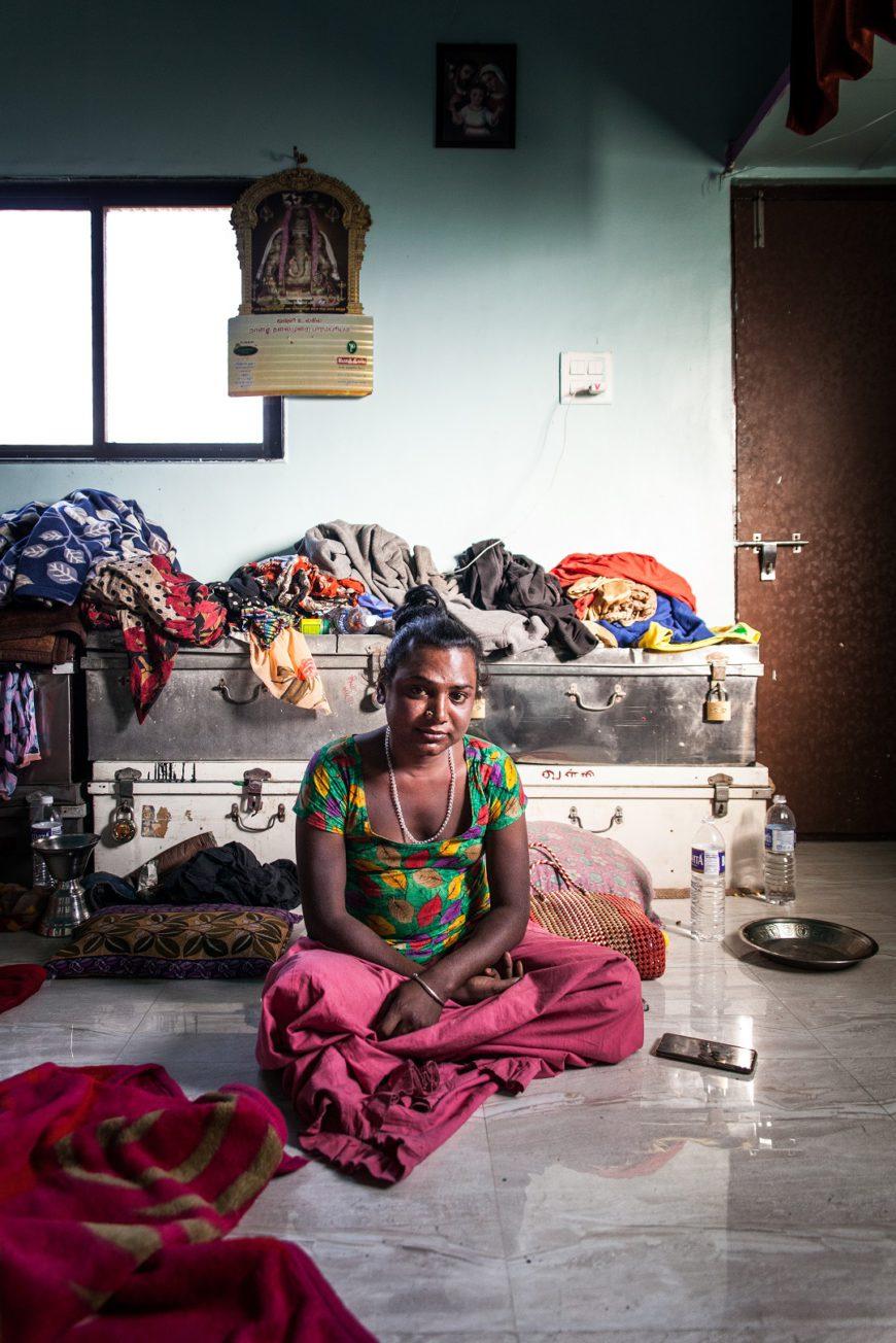 una mujer, en el centro de la imagen, posa sentada en el suelo de una habitación