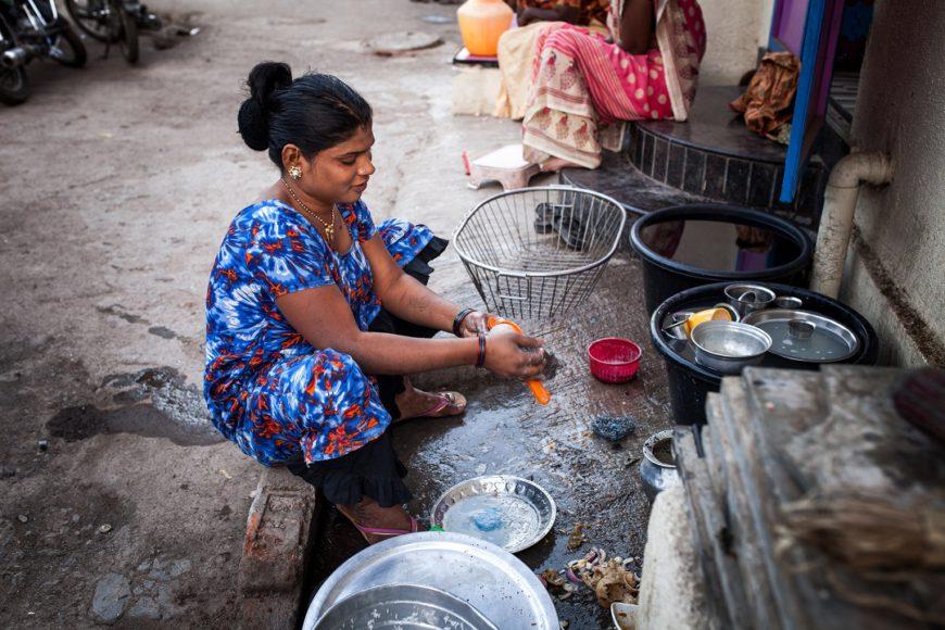 Vidas hijra. una mujer de cuclillas en el suelo está lavando los cacharros