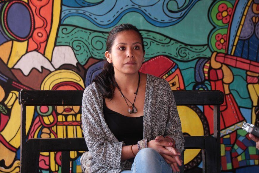una mujer sentada delante de un colorido mural