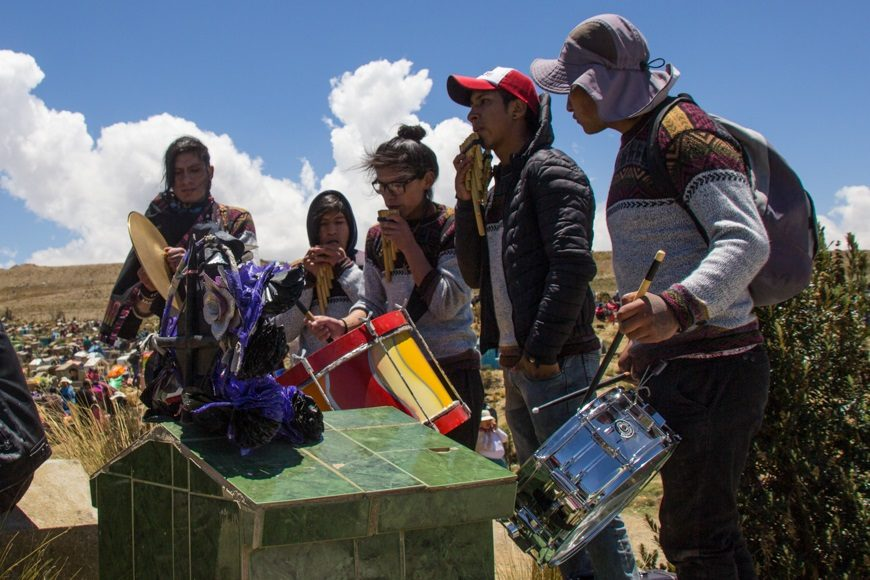 un grupo de personas tocan instrumentos en un cementerio de Bolivia