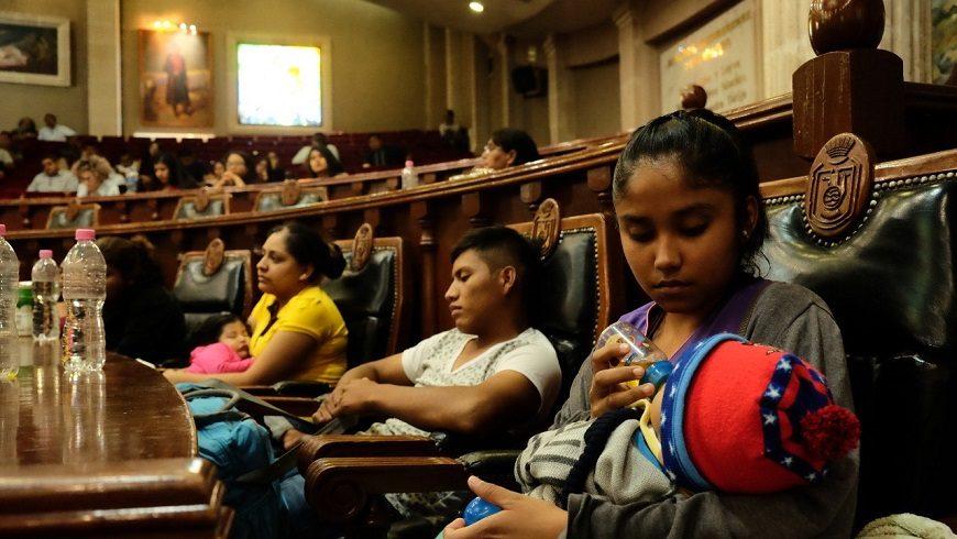 personas sentadas en la tribuna de un tribunal, en un primer plano una mujer da el biberón a un bebé