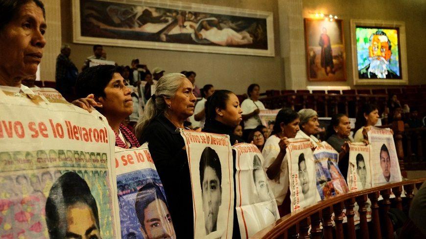 varias mujeres en fila sostienen carteles con fotos de mujeres