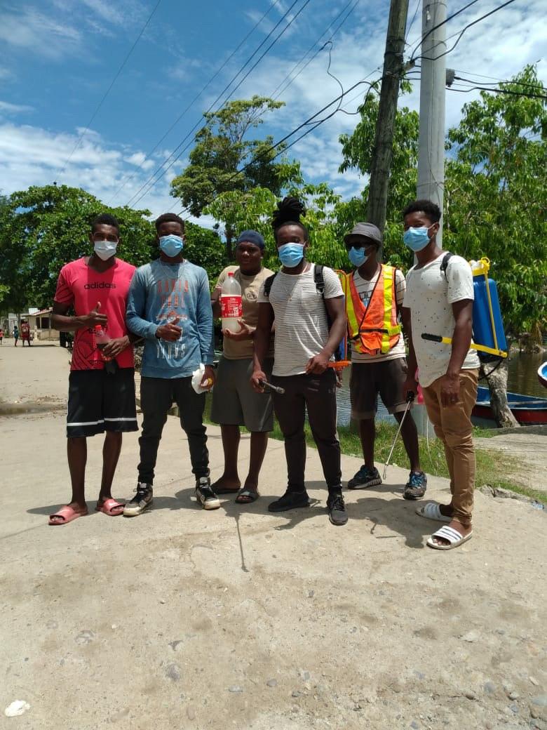 seis jóvenes con mascarilla posan en la calle para la foto, llevan materiales para fumigar