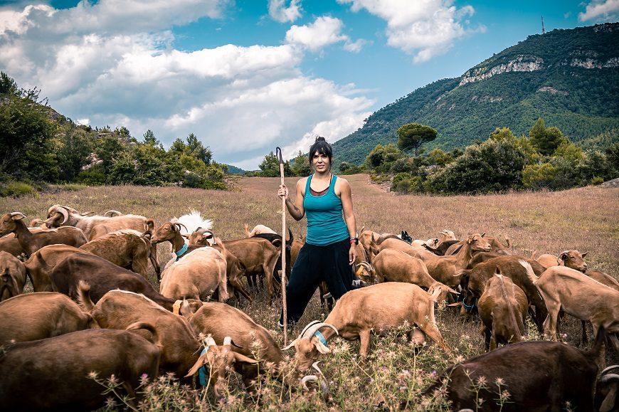 una ganadera en medio del campo y rodeada de sus cabras