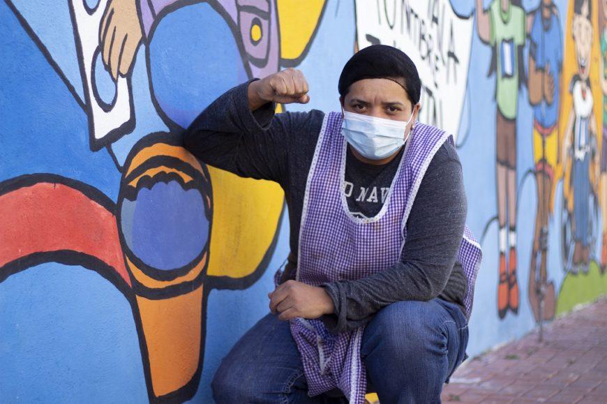 una persona agachada y con el brazo en el alto posa junto a un mural