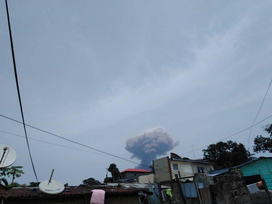 se ve el cielo y una nube de una explosión, sobre los tejados de casas